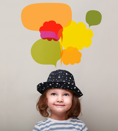 Dreaming kid girl in hat smiling and looking up on many colorful bright bubbles on grey background photo