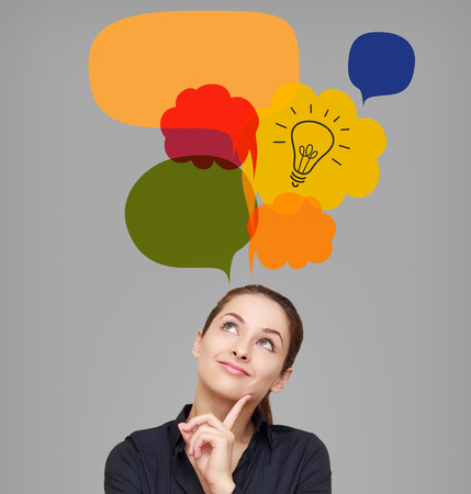 bright ideas: Business woman looking up on idea bulb in color bright bubble on grey background