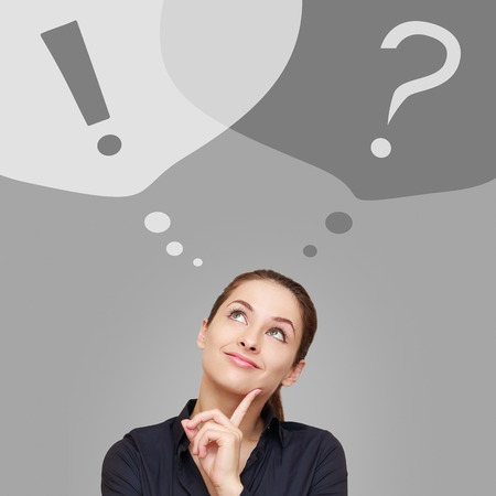 woman looking up: Thinking business woman looking up on question and exclamation signs in bubbles on grey background