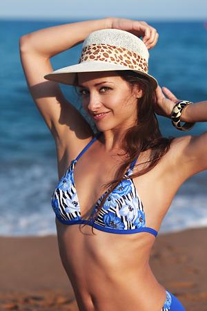 beautiful armpit: Beautiful bikini woman with epilation armpit on blue sea background looking with happy smile