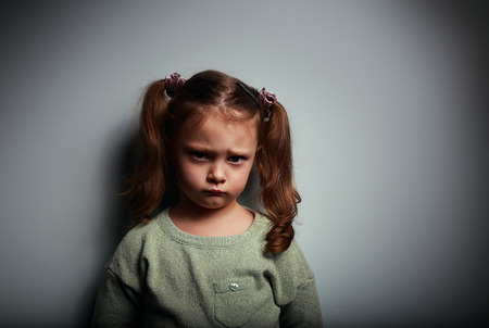 frustration girl: Sad kid girl looking with very unhappy face on dark background