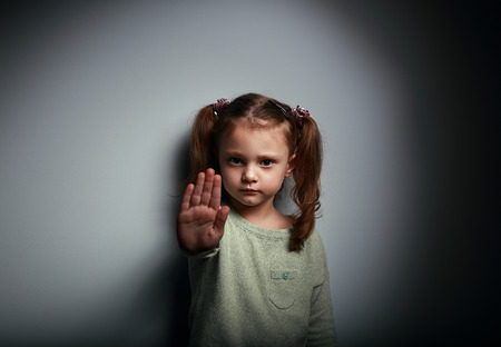 anger kid: Kid girl showing hand signaling to stop useful to campaign against violence and pain on dark background with empty copy space Stock Photo