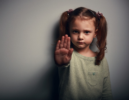 abused: Angry kid girl showing hand signaling to stop useful to campaign against violence and pain on dark background. Closeup portrait Stock Photo
