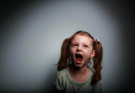 Boos kind meisje schreeuwen met geopende mond en kijken met kwaad op donkere achtergrond