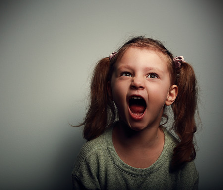 anger kid: Shouting angry kid girl with open mouth and negative look on dark background Stock Photo