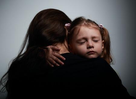 Sad fille pleurer étreignant sa mère avec le visage triste sur fond sombre ombres