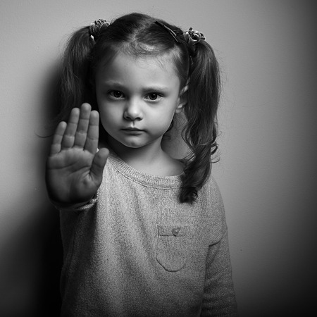 woman stop: Stop violence against kids. Serious kid showing hand stop sign. Black and white portrait