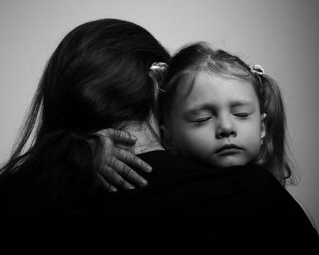 Depressie dochter knuffelen haar moeder met droevig gezicht. Close-up portret zwart en wit Stockfoto