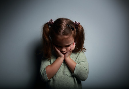 Crying kid girl holding the face the hands and looking down on dark background Stock Photo