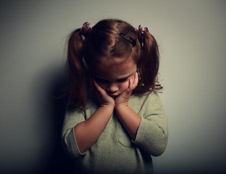 Sad crying alone kid girl on dark background. Closeup portrait Stock Photo