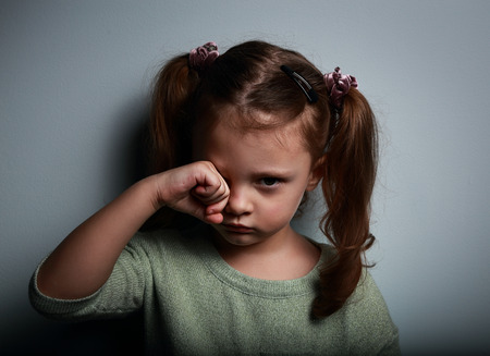 crying eyes: Crying kid girl with hand near eyes looking unhappy on dark background