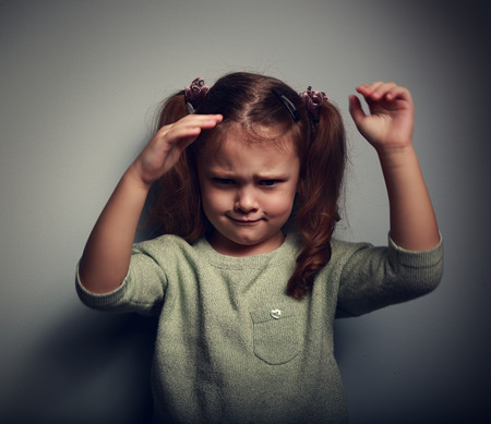 emotional stress: Very angry kid girl looking aggressive and waving the arms on dark background. Closeup portrait Stock Photo
