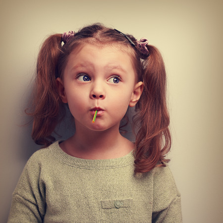 wonder: Fun girl eating candy with surprising thinking big eyes. Vintage closeup portrait Stock Photo