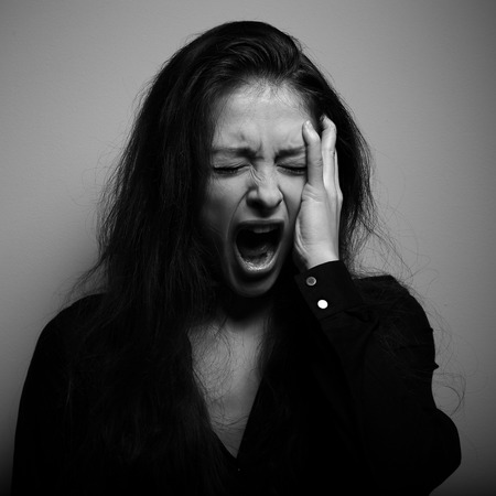 Shouting woman with unhappy, depressed crying face in big drief. Black and white portrait