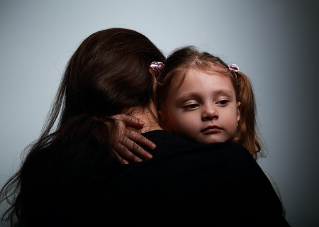 ojos tristes: Pequeña hija triste que abraza a su madre con amor sobre fondo oscuro