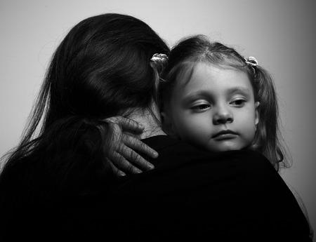 petite fille triste: mode de vie de famille. Fille embrassant sa m�re et l'air grave. Portrait en noir et blanc