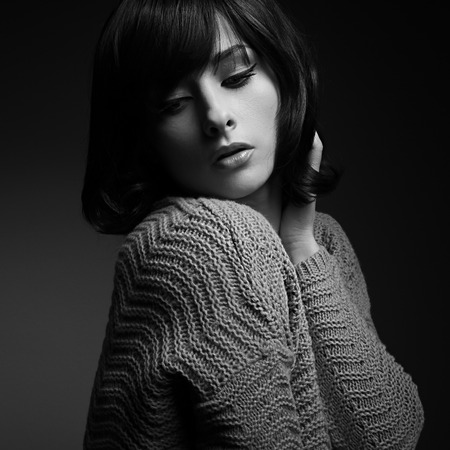Beautiful makeup female model with short hair style posing in knitted sweater. Black and white portrait on dark shadows background photo