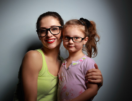 Happy mother and cute girl in fashion black glasses looking with love on dark background