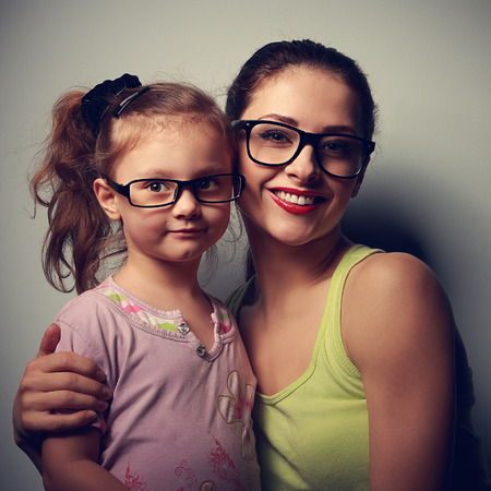 Smiling woman and happy kid girl in eyeglasses looking happy. Closeup portrait