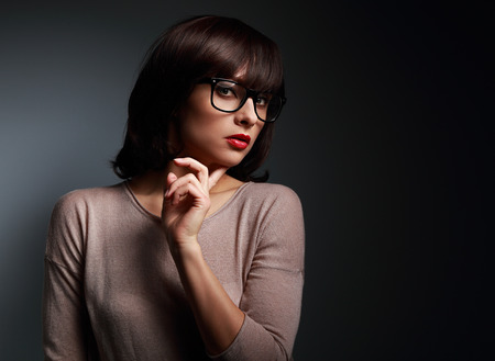 Sexy business thinking woman looking in fashion eyes glasses on black background Stock Photo