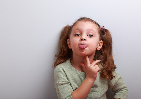 grimacing: Thinking grimacing girl showing tongue with finger under face and looking funny in camera with empty copy space Stock Photo