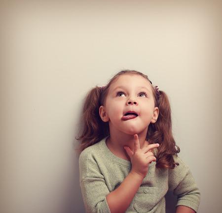 dudas: Pensando chico divertido que muestra la lengua y la celebración de dedo bajo la cara mirando hacia arriba en el espacio vacío de copia. Retrato del color de la vendimia