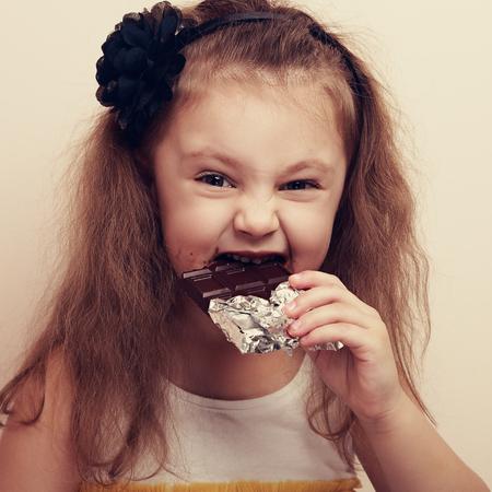 craving: Smiling kid girl biting dark chocolate with craving fun eyes. Vintage closeup portrait Stock Photo