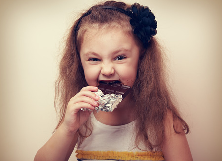 young: Happy fun smiling kid girl biting dark chocolate with craving eyes. Vintage closeup portrait Stock Photo