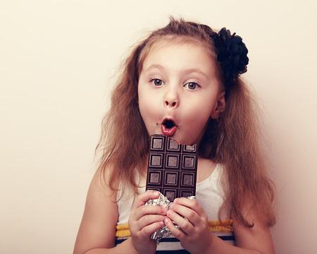 personas mirando: Muchacha sorprendida con la boca abierta la celebraci�n de chocolate y mirando. Vintage retrato de cerca