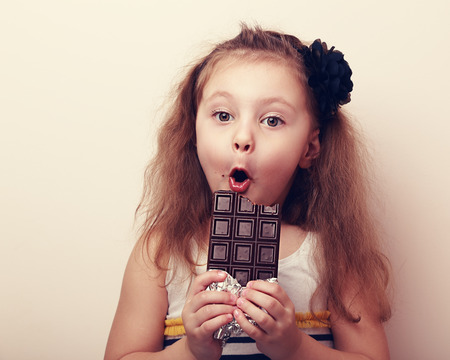 1 person: Surprised girl with open mouth holding chocolate and looking. Vintage closeup portrait
