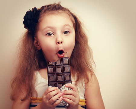 Surprised funny girl with open mouth and big eyes holding chocolate and looking. Vintage closeup portrait with empty copy space Stock Photo