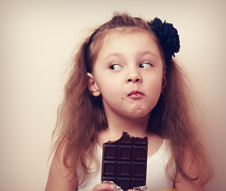 Thinking humor kid face eating chocolate and looking. Closeup vintage portrait