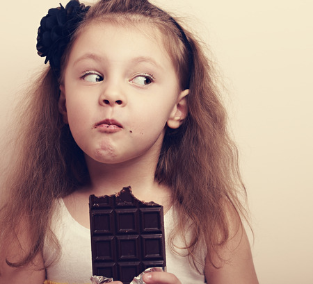 Thinking expression kid girl eating chocolate and looking fun. Closeup instagram portrait Stok Fotoğraf