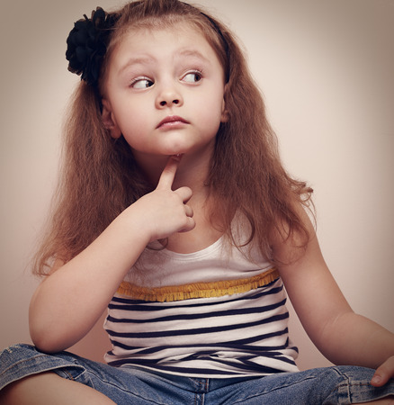 keek: Thinking prying kid girl sitting in jeans with finger under face. Closeup vintage portrait Stock Photo