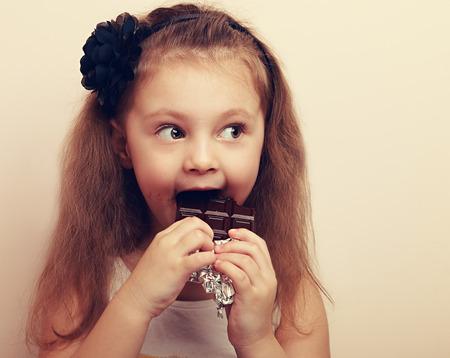 surprised kid: Fun surprised kid girl biting dark chocolate. Vintage closeup portrait with empty copy space