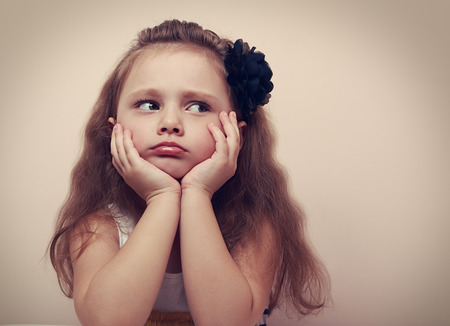 personne en colere: Belle fille regardant triste aux l�vres moue. Portarit Gros plan d'enfant mignon avec les cheveux longs. VIntage