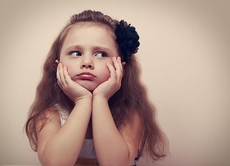 Krásná dívka hledá smutný s našpulené rty. Prohlíží portarit roztomilé dítě s dlouhými vlasy. Ročník