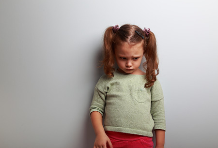 child stress: Unhappy abandoned kid girl looking down on blue background with empty copy space