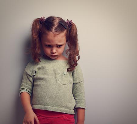 sad look: Abandonado niño triste mirando hacia abajo con el dolor en la cara. Retrato de la vendimia del primer con el espacio vacío de la copia