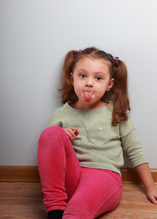 grimaces: Fun girl showing the tongue sitting on the floor on blue wall background