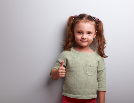 little finger: Happy girl showing thumb up sign on blue background with empty copy space