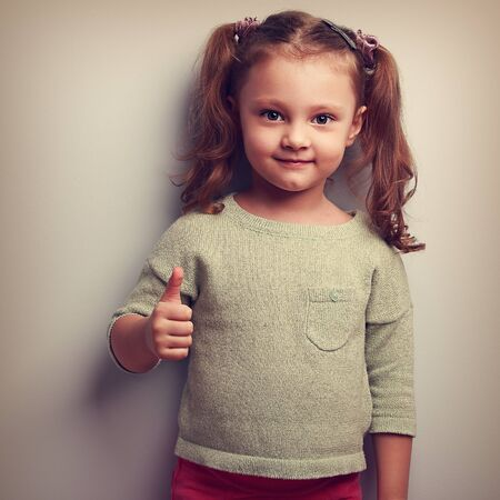 ok symbol: Smiling girl showing thumb up sign and looking happy. Vintage closeup portrait