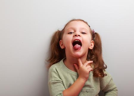 思考遊び心のある子供の女の子が舌を示します。空のコピー スペースとポートレート、クローズ アップ