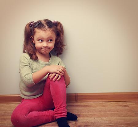bambini pensierosi: Ragazza di pensiero umorismo seduta sul pavimento in abiti di moda. Vintage ritratto del primo piano con copia spazio vuoto