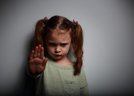 Kid chica mostrando señalización para detener la violencia y el dolor y mirando hacia abajo sobre fondo oscuro con el espacio vacío de la copia a mano