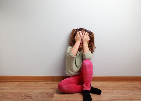Huilende ongelukkige jongen meisje zittend op de vloer met gesloten gezicht met lege kopie ruimte Stockfoto