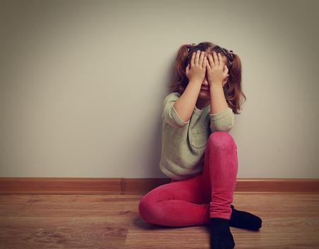 violencia intrafamiliar: Asustado llorando ni�a ni�o sentado en el suelo con la cara cerrado las manos. Vintage retrato de cerca