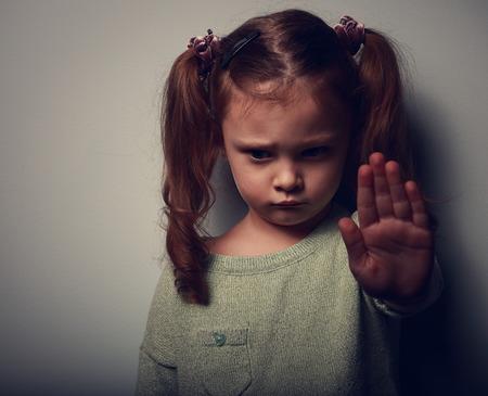 violencia intrafamiliar: Kid chica mostrando señalización para detener la violencia y el dolor y mirando hacia abajo sobre fondo oscuro mano. Retrato de detalle de color Foto de archivo