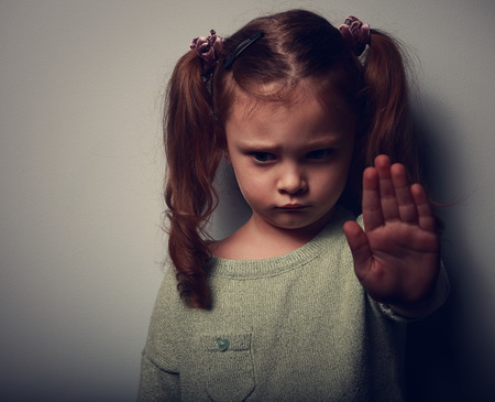 Kid girl showing hand signaling to stop violence and pain and looking down on dark background. Closeup color portrait