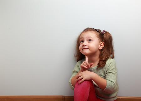 dudas: Muchacha de la diversión niño pensamiento sentado en jeans de color rosa y mirando para arriba en azul copia espacio de fondo